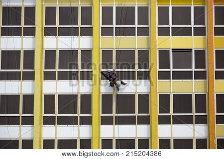 A lone window washer on a yellow high-rise building in Tel Aviv. Israel.