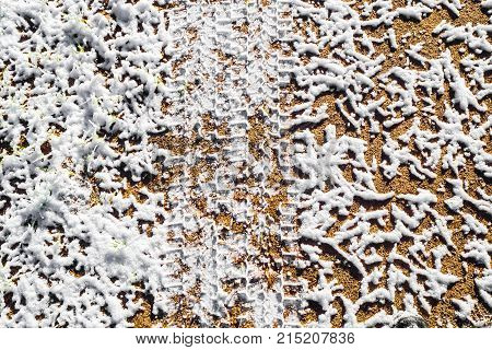 Texture is a print of tire on icy dirt road. Forest road after threat of cold weather and snow. The background of the snow surface.