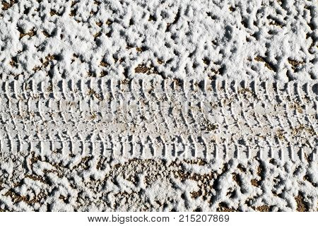The texture is a print of the tire on icy dirt road. Forest road after threat of cold weather and snow. The background of the snow surface.