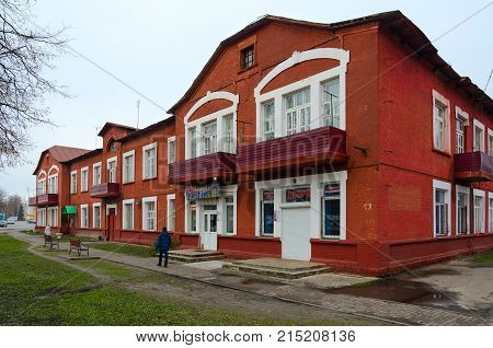 DOBRUSH BELARUS - NOVEMBER 20 2017: Unknown people walk along street near residential house of workers of paper-making factory (1st half of XX century) Dobrush Belarus