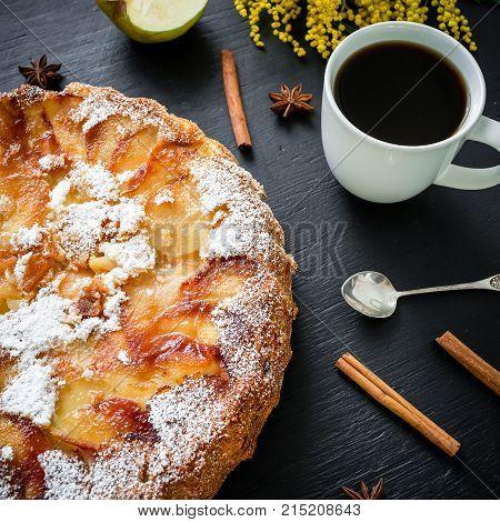Apple cake, coffee mug, apple, cinnamon and mimosa flowers on dark background. Flat lay, Top view. Charlotte