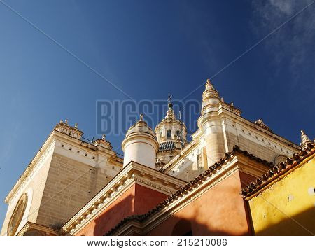 View of colourful walls and turrets of El Salvador church against a blue sky, Seville, Andalucia, Spain.
