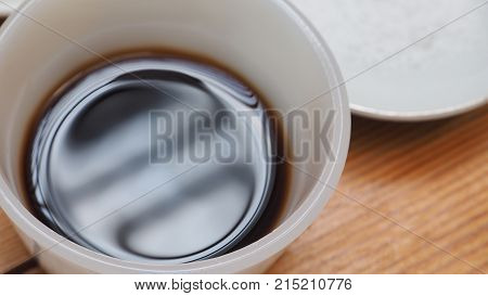 Soy sauce and salt in ceramic cup and plate to preparing for cook on wood desk Macro photo focus select at foreground of cup edge and sauce.