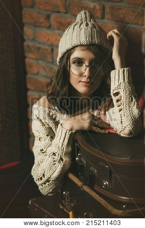 Modern hipster girl wearing glasses and knitted clothes in a room with brick walls. Loft style interior. Teenager girl in warm clothes.