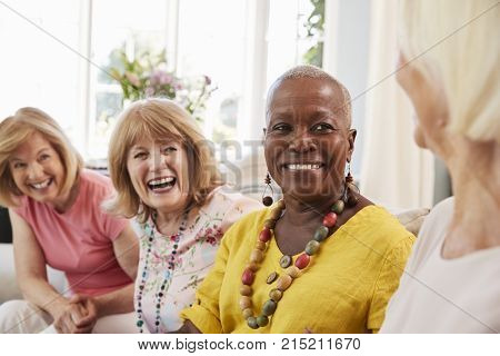 Group Of Senior Female Friends Relaxing On Sofa At Home