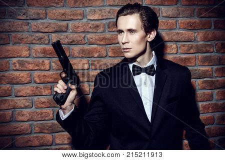 Handsome man in black suit holding a gun. Secret agent, mafia.