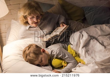 Portrait of smiling grandmother wearing glasses reading bedtime stories to sleeping little boy in dark room under lamplight