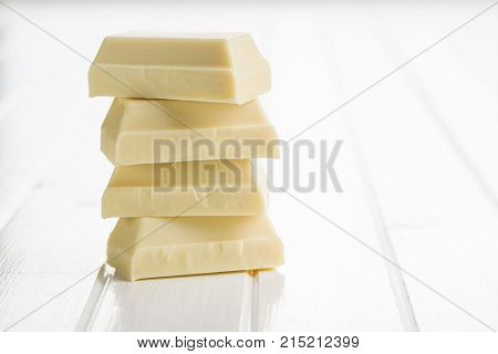Pile of white chocolate on white table.
