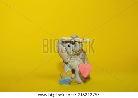Animals,Toys,Holidays Concept.Cute Little Toy on Yellow Background.Little Baby Elephant Toy with Pink Heart Standing over Yellow Background with a Lot of Copy Space. Baby Elephant Toy Holding Hearts.