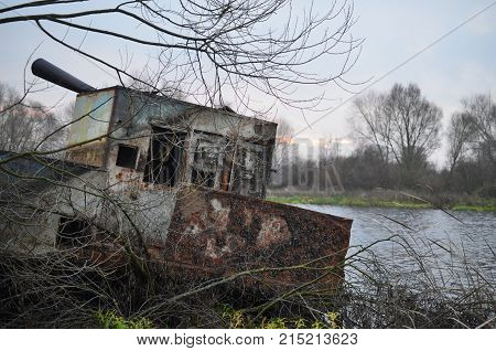 A dilapidated barge moored on the river bank
