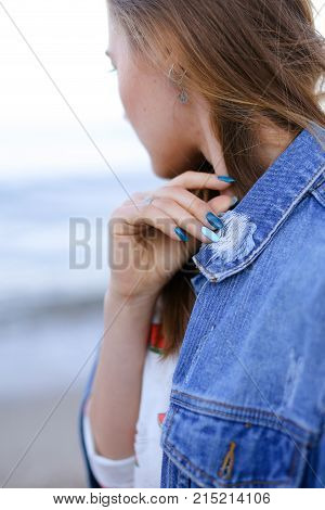 Shooting close-up portrait of wonderful young woman who stares into distance at sea waves and flirtatiously beckons with look, poses and smiles, enjoys fresh air, standing on shore of blue bottomless sea on summer sunny evening. Woman of European