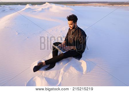 Young and handsome Muslim guy sits in social networks using computer, prints message or reads news, rests from turmoil of city, enjoys tranquility of sandy desert sitting on warm sand in open air on summer evening. Swarthy Muslim with short dark hair and