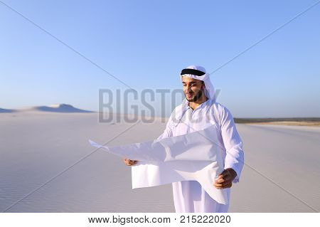 Beautiful Emirate Sheikh businessman studying project of future construction of complex, standing in middle of bottomless desert with white clean sand on clear warm day against blue sky. Swarthy Muslim with short dark hair dressed in kandura, long, spacio