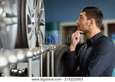 business, maintenance and people concept - male customer choosing alloy wheel rims at car repair service or auto store