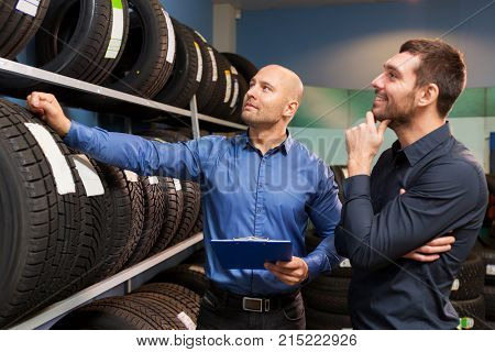 business, maintenance and people concept - male customer and salesman with clipboard showing wheel tires at car repair service or auto store