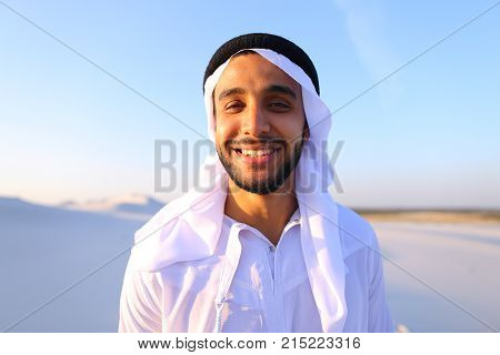 Close-up portrait of handsome Muslim young man who smiles and looks around, watching beauty of nature in sandy desert with white sand against blue sky in national suit that develops in wind. Swarthy Muslim with short dark hair dressed in kandura