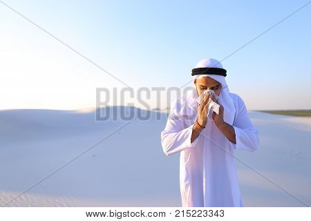 Sad handsome young man, sheikh ill with cold and feels unwell, eases breathing with handkerchief and looks to side, standing in middle of bottomless desert with snow-white sand on sunny summer day. Swarthy Muslim with short dark hair dressed in kandura