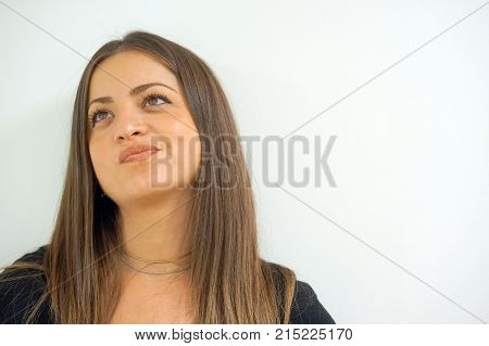 Beautiful female thinking and pondering over something looking aside on white background