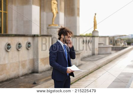 Cute Arabian guy talking with sweetheart girl by smartphone near Eiffel Tower. Handsome young mulatto man smiling and asking for date. Concept of romantic conversation with free online calls.