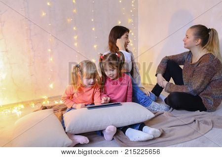 Two elder sister girls together with little girls younger sister spend time and talk with four of them, young women discuss affairs and gossip and watch children, two little girls play games on tablet, sit on floor in a bright room on background of wall w