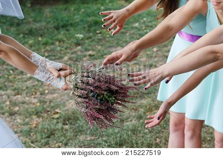 Bride tosses a bouquet to unmarried friends. Wedding traditions
