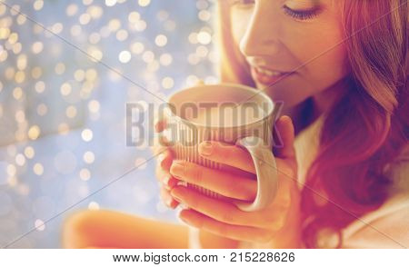 morning, coziness, winter and people concept - close up of happy young woman with cup of coffee or cocoa drink in bed at home