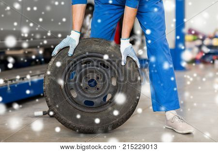 car service, repair, maintenance and people concept - auto mechanic man changing tire at workshop over snow