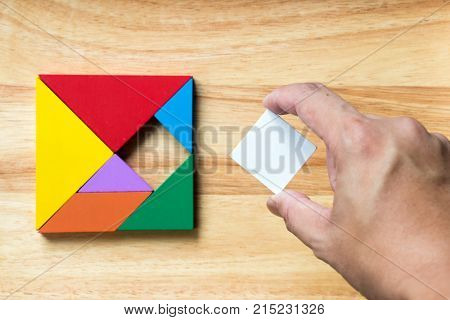 Color tangram puzzle in square shape that wait for fulfill on wood background