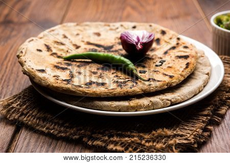 Bajra roti or Jowar Roti or Indian bread made using Bajra or Jowar, served with green chilly thecha