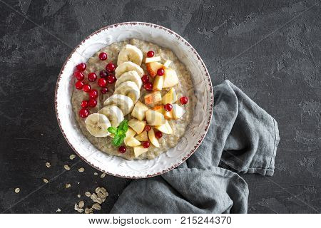 Oatmeal porridge with fruits and berries on plate, top view