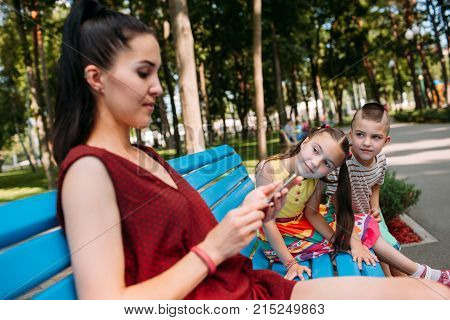 Children try to attract mother's attention at park. Business hinders spending time with family.