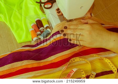 Dressmaker woman working with sewing machine. Sewing Process the sewing machine sew women's hands. sewing machine and female scissors