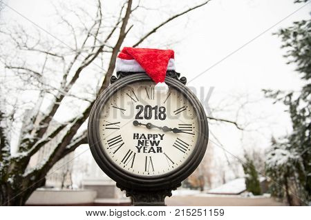 vintage old street clock with the inscription Happy New Year 2018 and Santa Claus hat on them outdoors in winter park