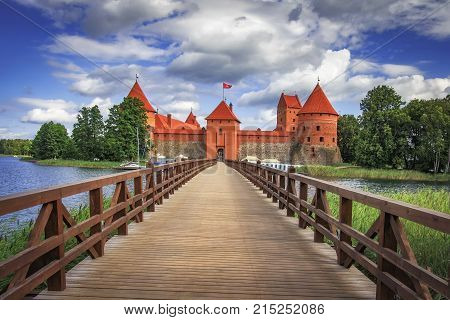 Trakai Castle in Lithuania on bright sunny day with blue sky and white clouds. Landscape of castle with bridge across lake. Castle on island