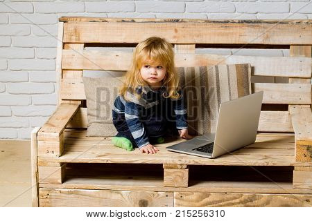 Small boy blogging on bench online buy. School and communication. Kid at computer with cell phone sms and 4G. Social network and new technology. child with laptop and mobile phone education.