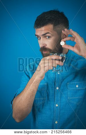 Treatment hypnotic tablet. painkiller drug and antidepressant. Man with beard hold water glass on blue background headache. Health and medicine flu and cold. Hipster drink pill with water illness.