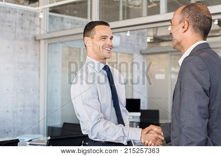 Smiling businessmen shaking hands while standing in modern office boardroom. Happy business men shaking hands and looking at each other. Handshake between mature leader and businessman after a deal.
