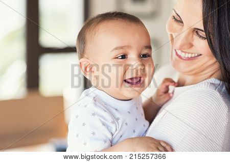 Portrait of a cute newborn baby in mother's hands. Beautiful mom holding cute son laughing. Closeup of mid woman with her little boy. New family and love concept.