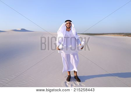 Beautiful Emirate Sheikh businessman studying project of future construction of complex, standing in middle of bottomless desert with white clean sand on clear warm day against blue sky. Swarthy Muslim with short dark hair dressed in kandura, long