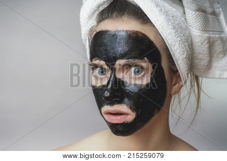 Black mask on woman face ,smiling ,skincare, cleansing pore ,against acne