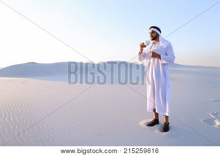 Portrait  confident and happy male Muslim who drinks invigorating coffee drink from white cup and enjoys calm morning, standing in midst of endless sandy desert with pure white sand in open air on warm summer morning.