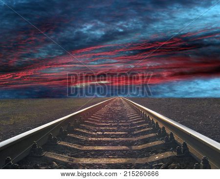 rails going away into the gloomy landscape. Black and white image with rails going away into the dark sky landscape