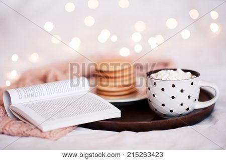 Cup of coffee with marshmallow stay on wooden tray with open book and pancakes in bed over Christmas lights. Good morning. Breakfast.