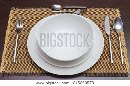 empty wihte dinner plates and utensils on dark wooden dining table good for food or meal concept