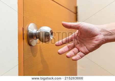 male hand reaching out to grab a door knob good for coming home home safety or intruder concept