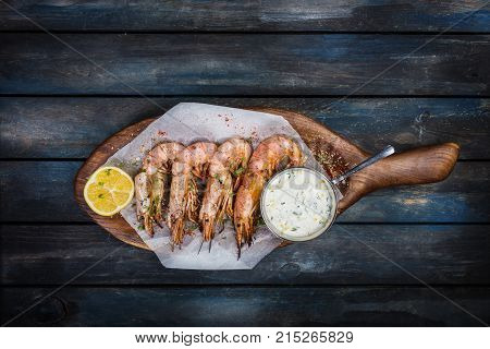 Large red Argentine shrimp or langoustine with white sauce and half a lemon on a wooden board. Top view.