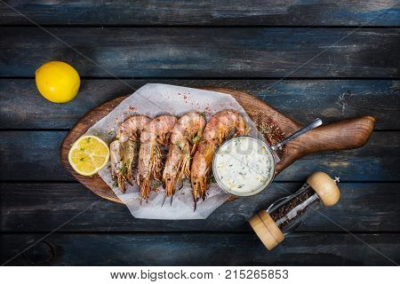 Delicious Argentine shrimp or langoustine with white sauce pepper-pot and half a lemon on a wooden board. Top view.