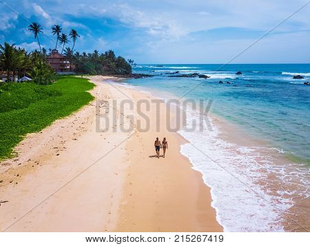 Couple walks on tropical sandy beach with palm trees on the background. Aerial shot. Vacation and honeymoon concept