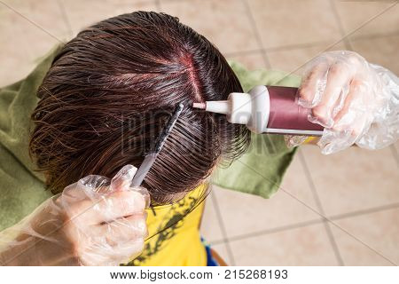 Woman Attempting To Apply Chemical Hair Color Onto Scalp