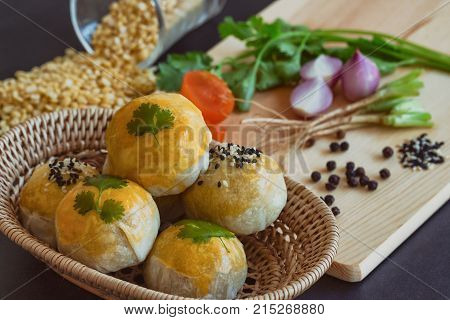 Chinese pastry or moon cake on wood basket with some ingredient on wood cutting board. Delicious mooncake or Chinese pastry put on black granite table in top view close up. Homemade bakery concept of Chinese pastry or mooncake.